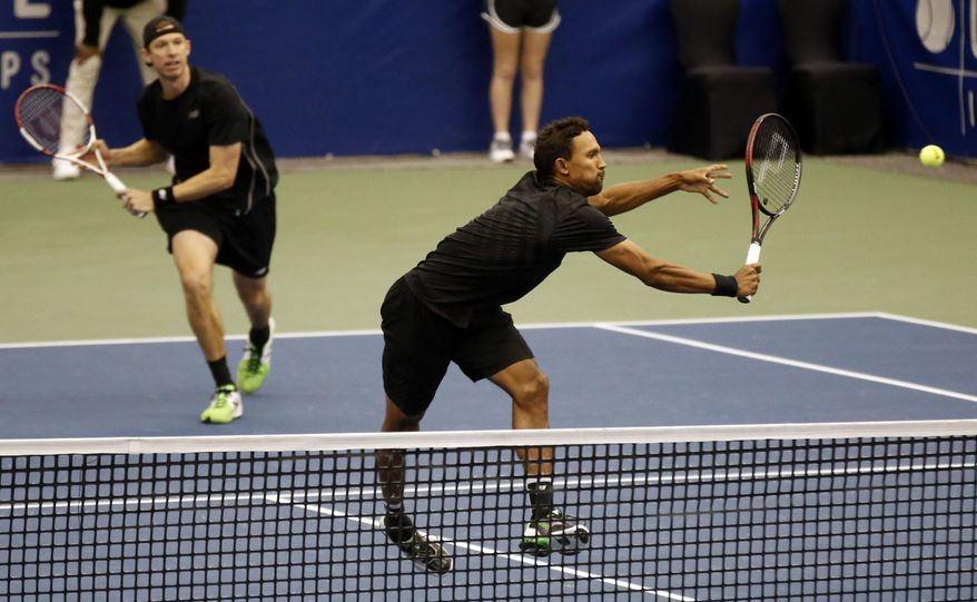 Raven Klaasen, front, of South Africa, returns to Mike and Bob Bryan as Eric Butorac watches in the finals at the U.S. National Indoor Tennis Championships, Sunday, Feb. 16, 2014 in Memphis, Tenn. Klaasen and Butorac won 6-4, 6-4. (AP Photo/Rogelio V. Solis)