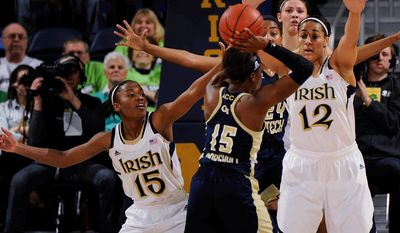 Georgia Tech guard Tyaunna Marshall tries to pass around Notre Dame guard Lindsay Allen, left, and Taya Reimer during  the first half of an NCAA college basketball game, Monday, Feb. 17, 2014, in South Bend, Ind. (AP Photo/Joe Raymond)