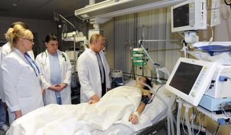 In this photo provided by RIA Novosti Kremlin, Russian President Vladimir Putin, center, speaks to skier Maria Komissarova in a hospital in Krasnaya Polyana, Russia, on Saturday, Feb. 15, 2014. The 23-year-old Russian ski cross racer fractured her spine during a training session Saturday and underwent a 6 1/2 hour surgery. (AP Photo/RIA Novosti, Mikhail Klimentyev, Presidential Press Service)