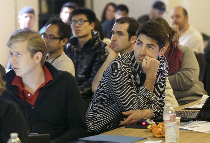 ** FILE ** In this Saturday, Feb. 8, 2014, photo, Segah Meer, right, and other participants listen to speakers during the FinCapDev San Francisco Hackathon in San Francisco. (AP Photo/Jeff Chiu)