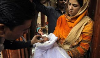 ** FILE ** In this Feb. 2, 2014 photo, a Pakistani health worker vaccinates a child against polio, in Peshawar, Pakistan. Pakistan's beleaguered battle to eradicate polio is threatening a global, multi-billion dollar campaign to wipe out the disease worldwide. Because of Pakistan, the virus is spreading to countries that were previously polio-free, U.N. officials say. (AP Photo/Mohammad Sajjad)