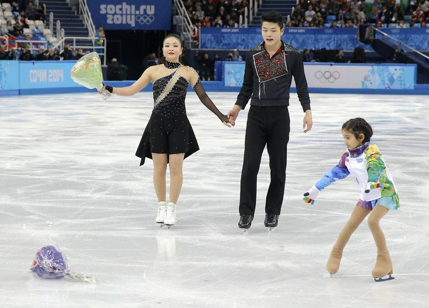 A flower girl goes to pick up a bouquet thrown onto the ice by spectators as Maia Shibutani and Alex Shibutani of the United States leave the ice after competing in the ice dance free dance figure skating finals at the Iceberg Skating Palace during the 2014 Winter Olympics, Monday, Feb. 17, 2014, in Sochi, Russia. (AP Photo/Vadim Ghirda)