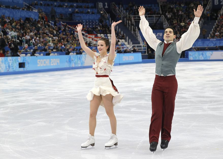 Anna Cappellini and Luca Lanotte of Italy wave to spectators as they leave the ice after competing in the ice dance free dance figure skating finals at the Iceberg Skating Palace during the 2014 Winter Olympics, Monday, Feb. 17, 2014, in Sochi, Russia. (AP Photo/Vadim Ghirda)