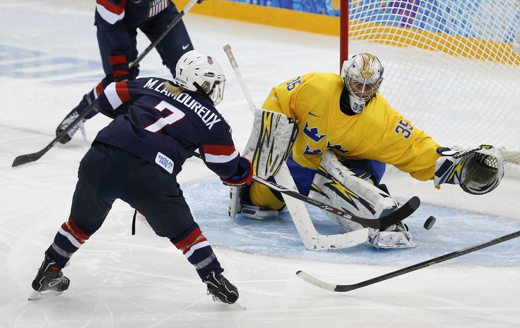 Monique Lamoureux of the United States takes  shot against Goalkeeper Valentina Wallner of Sweden during the second period of the 2014 Winter Olympics women's semifinal ice hockey game at Shayba Arena Monday, Feb. 17, 2014, in Sochi, Russia. (AP Photo/Julio Cortez)