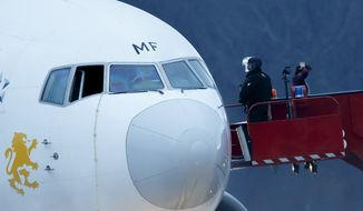 Police stand on the stairs after passengers were evacuated from a hijacked Ethiopian Airlines Plane on the airport in Geneva, Switzerland, Monday, Feb. 17, 2014.The  aircraft traveling from Addis Abeda, Ethiopia, to Rome, Italy, has landed at Geneva's international airport early Monday morning. Swiss authorities have arrested the co-pilot.  (AP Photo/Keystone, Salvatore Di Nolfi)