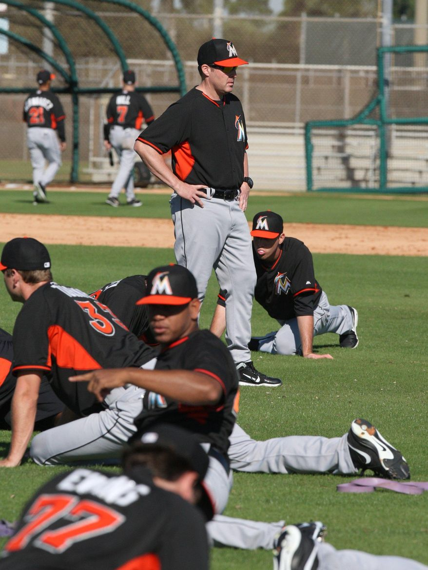 Miami Marlins manager Mike Redmond checks on the players during the second day of spring training baseball, Monday, Feb. 17, 2014 at Roger Stadium in Jupiter, Fla. (AP Photo/El Nuevo Herald, Hector Gabino)
