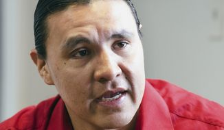 In this Feb. 6, 2014 photo, Chase Iron Eyes, an attorney and American Indian activist on the Standing Rock Reservation, is seen in Fort Yates, N.D., talking about being less dependent on propane and finding alternative ways to heat houses on the reservation.  As many as 5,000 homes on the reservation that straddles the North Dakota-South Dakota border rely on propane for heat. Iron Eyes is spearheading a pilot program that would outfit reservation homes with heat stoves that burn pellets made from natural materials. (AP Photo/Kevin Cederstrom)