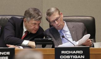 Terrence McGuire, who is a proxy for California Public Employees Retirement System Board Member, State Controller John Chiang, talks with board member Richard Costigan, during a meeting in Sacramento, Calif., Tuesday, Feb. 18, 2014. The board of the nations largest public pension agreed to Gov. Jerry Brown's request to accelerate the state's payments starting this summer, but cities counties and school districts' rates won't change until 2016. The board approved new assumptions for its pension system effectively increasing contribution rates. (AP Photo/Rich Pedroncelli)