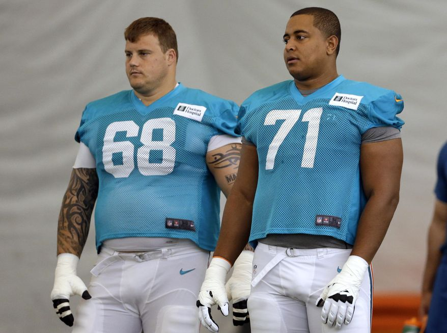 FILE - In this July 24, 2013, file photo, Miami Dolphins guard Richie Incognito (68) and tackle Jonathan Martin (71) stand on the field during NFL football practice in Davie, Fla. Pending free agency and a racially charged bullying scandal could add up to a completely overhauled Miami Dolphins offensive line and some players looking for a job. Several Miami linemen are at the center of the NFL-ordered report, including Incognito, Martin, John Jerry and Mike Pouncey. (AP Photo/Lynne Sladky, File)