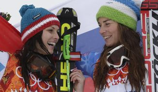 Women's giant slalom winners Austria's Anna Fenninger (silver), left, and Slovenia's Tina Maze (gold), right, pose for photographers on the podium at the Sochi 2014 Winter Olympics, Tuesday, Feb. 18, 2014, in Krasnaya Polyana, Russia.(AP Photo/Gero Breloer)