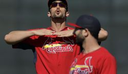 St. Louis Cardinals' Matt Carpenter, left, talks with teammate Daniel Descalso while warming up at the start spring training baseball practice Tuesday, Feb. 18, 2014, in Jupiter, Fla. (AP Photo/Jeff Roberson)