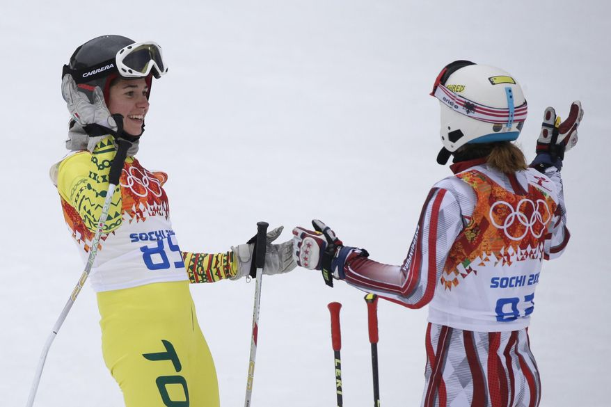Togo's Alessia Afi Dipol and Albania's Suela Mehilli celebrate after completing the first run in the women's giant slalom at the Sochi 2014 Winter Olympics, Tuesday, Feb. 18, 2014, in Krasnaya Polyana, Russia. (AP Photo/Gero Breloer)