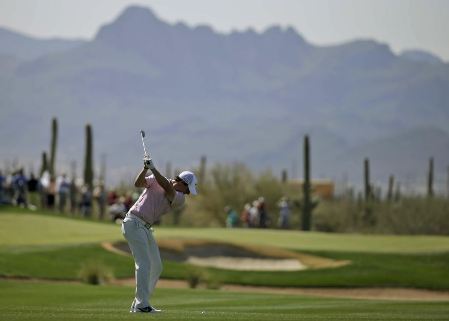 Rory McIlroy, of Northern Ireland, hits from the fairway on the 17th hole during a practice round for the Match Play Championship golf tournament Tuesday, Feb. 18, 2014, in Marana, Ariz. (AP Photo/Chris Carlson)