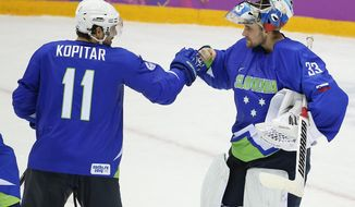 Slovenia forward Anze Kopitar bumps fists with goaltender Robert Kristan after Slovenia beat Austria 4-0 in a men's ice hockey game at the 2014 Winter Olympics, Tuesday, Feb. 18, 2014, in Sochi, Russia. Slovenia advanced to the quarterfinals. (AP Photo/Julio Cortez)