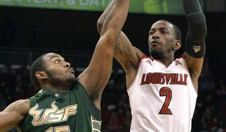 Louisville's Russ Smith, right, puts a shot up over the defense of South Florida's Shemiye McLendon during the second half of an NCAA college basketball game, Tuesday, Feb. 18, 2014, in Louisville, Ky. Louisville defeated So. Florida 80-54. (AP Photo/Timothy D. Easley)