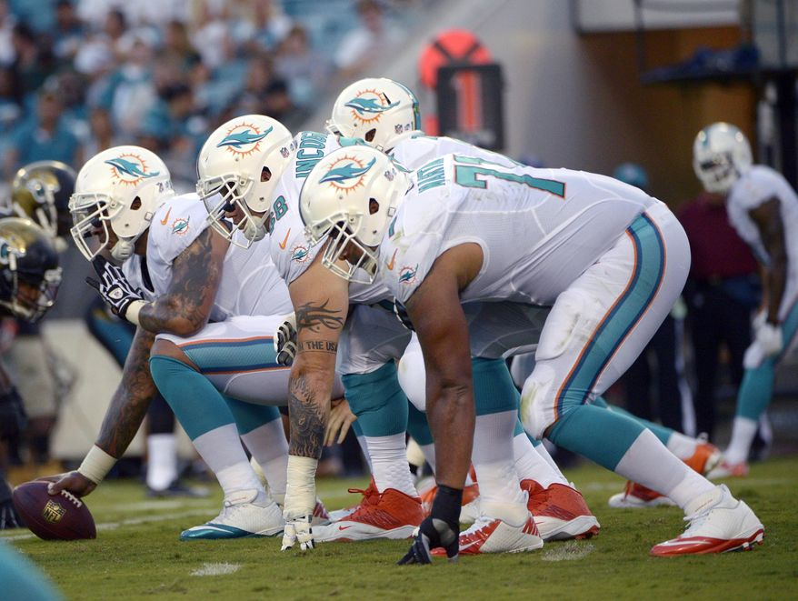 """FILE - In this Aug. 9, 2013, file photo, Miami Dolphins center Mike Pouncey, left, guard Richie Incognito (68) and tackle Jonathan Martin (71) set up to block during the first half of an NFL preseason football game against the Jacksonville Jaguars in Jacksonville, Fla. Martin was subjected to """"a pattern of harassment"""" that included racist slurs and vicious sexual taunts about his mother and sister by three teammates, according to a report ordered by the NFL.  The report said Incognito, who was suspended by the team in November, and fellow offensive linemen John Jerry and Pouncey harassed Martin.(AP Photo/Phelan M. Ebenhack)"""
