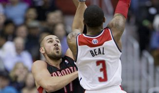 Toronto Raptors Jonas Valanciunas (17) of Lithuania defends as Washington Wizards Bradley Beal (3) shoots the ball and scores during the first half of an NBA basketball game in Washington, Tuesday, Feb. 18, 2014. (AP Photo/Manuel Balce Ceneta)
