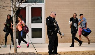 Students leave campus behind an armed police officer after a youth with two pistols was apprehended near the front of Chamblee Charter High School, according to authorities, on Tuesday, Feb. 18, 2014, in Chamblee, Ga., a suburb northeast of Atlanta. Chamblee City Manager Marc Johnson said a 16-year-old boy that had been suspended from the school was arrested without incident and police found a stash of additional weapons in the nearby woods, allegedly from a burglary earlier in the day. (AP Photo/David Tulis)