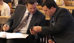 Kansas Secretary of State Kris Kobach, left, and state Rep. Brett Hildabrand, right, R-Shawnee,  confer during a House committee hearing on a health care bill they support, Tuesday, Feb. 18, 2014, at the Statehouse in Topeka, Kan. The bill would bring Kansas into a compact of states seeking to exempt themselves from federal health care laws. (AP Photo/John Hanna)