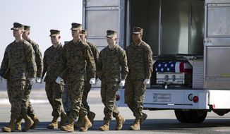 The transfer case containing the remains of Marine Master Sgt. Aaron C. Torian, of Paducah, Ky., is placed in a transfer vehicle, upon arrival at Dover Air Force Base, Del., on Tuesday, Feb. 18,  2014. The Department of Defense announced the death of Torian, who was supporting Operation Enduring Freedom in Afghanistan. ( AP Photo/Jose Luis Magana)