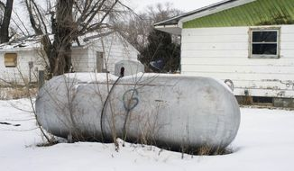 FILE - In this Feb. 6, 2014 file photo, a propane tank is seen outside a home on the Standing Rock Reservation in Fort Yates, N.D. On Monday, Feb. 17, 2014, Standing Rock Chairman Dave Archambault II said the propane crisis on the reservation is easing thanks to warmer weather and a drop in the price of the fuel, as well as federal assistance and a charitable donation. As many as 5,000 homes on the reservation that straddles the North Dakota-South Dakota border rely on propane for heat. (AP Photo/Kevin Cederstrom, File)