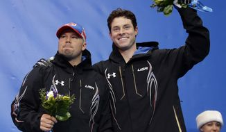 The team from the United States USA-1, piloted by Steven Holcomb and brakeman Steven Langton, celebrate their bronze medal win after the men's two-man bobsled competition at the 2014 Winter Olympics, Monday, Feb. 17, 2014, in Krasnaya Polyana, Russia. (AP Photo/Dita Alangkara)