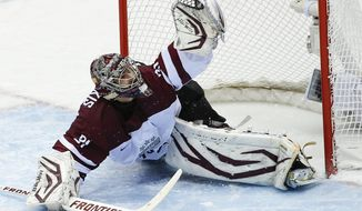 Latvia goaltender Edgars Masalskis snags a shot on goal by Switzerland in the second period of a men's ice hockey game at the 2014 Winter Olympics, Tuesday, Feb. 18, 2014, in Sochi, Russia. (AP Photo/Julio Cortez)
