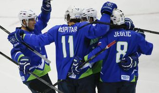 Slovenia forward Anze Kopitar (11) celebrates with teammates after scoring a goal against Austria in the first period of a men's ice hockey game at the 2014 Winter Olympics, Tuesday, Feb. 18, 2014, in Sochi, Russia. (AP Photo/Julio Cortez)