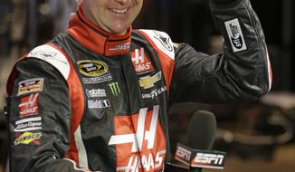 Driver Kurt Busch laughs while talking with a TV crew before an interview during NASCAR auto racing media day at Daytona International Speedway in Daytona Beach, Fla., Thursday, Feb. 13, 2014. (AP Photo/John Raoux)