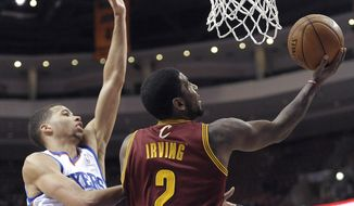 Cleveland Cavaliers' Kyrie Irving (2) drives to the basket as Philadelphia 76ers' Michael Carter-Williams defends during the first half of an NBA basketball game, Tuesday, Feb. 18, 2014, in Philadelphia. (AP Photo/Michael Perez)
