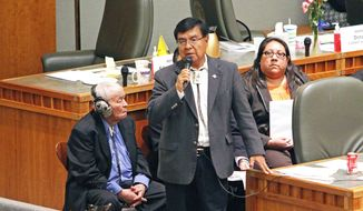 Rep. James Roger Madalena speaks on the Navoajo Nation's gambling agreement while Sen. John Pinto, left, and Attorney Karis N. Begaye, right listen on the House floor at the state Capitol, Tuesday, Feb. 18, 2014, in Santa Fe, N.M. The New Mexico House approved the tribal-state compact that would allow the Navajos to open three additional casinos over 15 years. The proposal goes to the Senate for consideration. Lawmakers adjourn on Thursday. (AP Photo/The Santa Fe New Mexican, Jane Phillips)