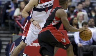 Washington Wizards center Marcin Gortat (4) of Poland, towers over Toronto Raptors point guard Kyle Lowry (7) as Lowry dribbles the ball during the second half of an NBA basketball game in Washington, Tuesday, Feb. 18, 2014. The Raptors won 103-93. (AP Photo/Manuel Balce Ceneta)