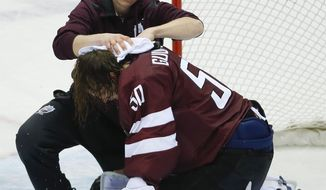 A trainer treats Latvia goaltender Kristers Gudlevskis after a collision with a Canadian player during the third period of a men's quarterfinal ice hockey game at the 2014 Winter Olympics, Wednesday, Feb. 19, 2014, in Sochi, Russia. Canada won 2-1. (AP Photo/Mark Humphrey)