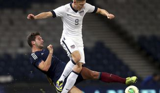 FILE - In this Nov. 15, 2013, file photo, United States' Aron Johannsson, right, vies for the ball with Scotland's Charlie Mulgrew, left, during an international soccer match at Hampden Park, Glasgow, Scotland. Johannsson is relatively new to the U.S. national team. The 23-year-old was born in Alabama to Icelandic parents, but moved back to Iceland in his youth and was a member of that nation's under-21 national side. He missed out on his first opportunity to play for Iceland's senior national team in late 2012 because of a groin injury and last year filed to make himself eligible to compete for the United States. (AP Photo/Scott Heppell, File)
