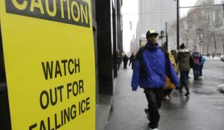 Pedestrians pass a sign warning them of falling ice near City Hall Tuesday, Feb. 18, 2014, in New York. Amid a brutal winter, New Yorkers are battling something far more dangerous than snow falling from the sky: ice tumbling from skyscrapers. (AP Photo/Frank Franklin II)