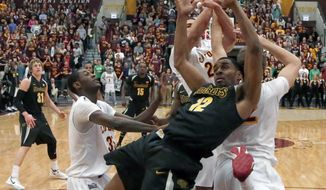Wichita State forward Darius Carter (12) battles Loyola of Chicago forward Matt O'Leary, right, and Nick Osborne, background as Milton Doyle, left, watches for a rebound during the first half of an NCAA college basketball game Wednesday, Feb. 19, 2014, in Chicago. (AP Photo/Charles Rex Arbogast)