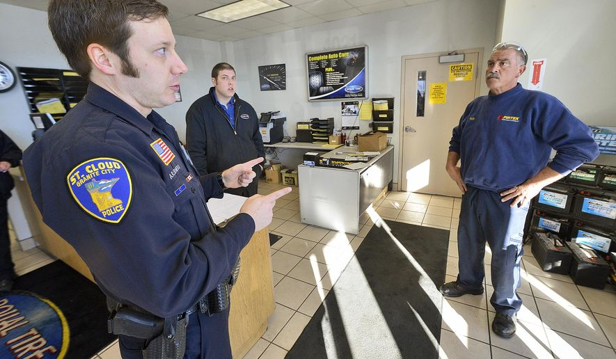 """St. Cloud Police Officer Alec Elness recounts the attempts to revive Rich Thies, right, after Thies suffered a heart attack as Tom Martins looks on,  Feb. 7, 2014 at Royal Tire on Roosevelt Road in St. Cloud, Minn.  The intervention that saved Thies' life was quicker, came initially by chance and from a series of strangers, some who do that for a living and others who just happened to be in the right place at the right time. Doctors rarely see a patient survive the """"widowmaker"""" heart attack that Thies had without immediate medical care.  (AP Photo/St. Cloud Times, Kimm Anderson)"""