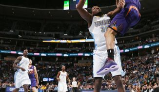 Phoenix Suns guard Gerald Green, right, flies over Denver Nuggets forward Kenneth Faried to dunk during the first quarter of an NBA basketball game in Denver on Tuesday, Feb. 18, 2014. (AP Photo/David Zalubowski)