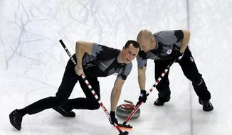 Canada's E.J. Harnden, left, and Ryan Fry, right, sweep ahead of the rock during the men's curling semifinal game against China at the 2014 Winter Olympics, Wednesday, Feb. 19, 2014, in Sochi, Russia. (AP Photo/Wong Maye-E)