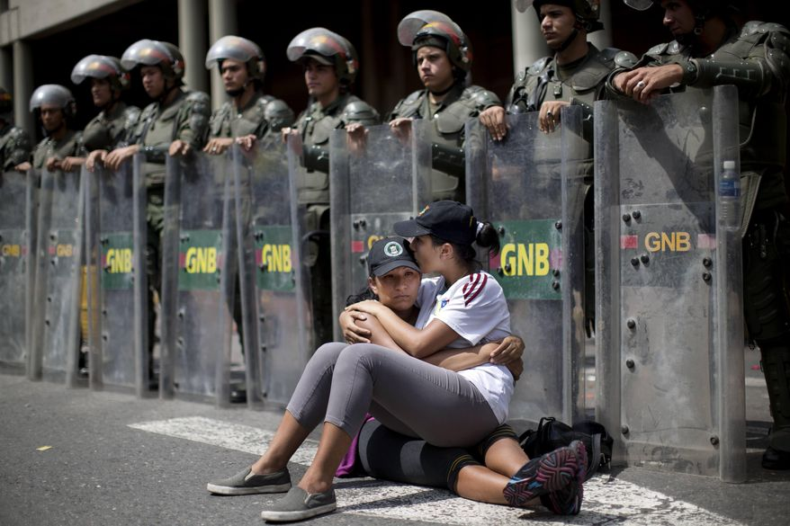 Women embrace as they sit in front of a line of National Bolivarian Guard outside the Palace of Justice court in Caracas, Venezuela, Wednesday, Feb. 19, 2014. Following a dramatic surrender and a night in jail, Venezuelan opposition leader Leopoldo Lopez was due in court Wednesday to learn what charges he may face for allegedly provoking violence during protests against the socialist government in the divided nation. (AP Photo/Rodrigo Abd)