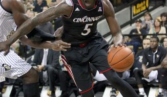 Central Florida forward Staphon Blair (52) defends against Cincinnati forward Justin Jackson (5) during the first half of an NCAA basketball game, Wednesday, Feb. 19, 2014, in Orlando Fla. (AP Photo Reinhold Matay)
