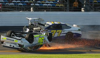 Parker Kligerman (30) slides on his roof after crashing during practice for Sunday's NASCAR Daytona 500 Sprint Cup Series auto race at Daytona International Speedway, Wednesday, Feb. 19, 2014 ,as Dave Blaney (77) drives past. (AP Photo/News-Journal, Nigel Cook)