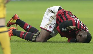 AC Milan's forward Mario Balotelli, lays on the turf after he injured himself in a collision during a round of 16th Champions League soccer match between AC Milan and Atletico Madrid at the San Siro stadium in Milan, Italy, Wednesday, Feb. 19, 2014. (AP Photo/Emilio Andreoli)