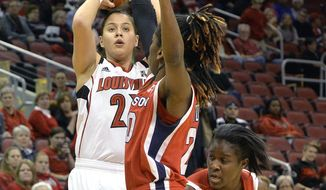 Louisville's Shoni Schimmel, left, puts up a shot over Houston's Yasmeen Thompson, center, and Alecia Smith during the first half of an NCAA college basketball game Wednesday, Feb. 19, 2014, in Louisville, Ky. Schimmel scored 15 points to become the second player to score over 2000 points in Louisville history. (AP Photo/Timothy D. Easley)