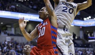 Xavier forward Justin Martin, right, fouls DePaul guard Brandon Young in the second half of an NCAA college basketball game, Wednesday, Feb. 19, 2014, in Cincinnati. Xavier won 83-64. (AP Photo/Al Behrman)