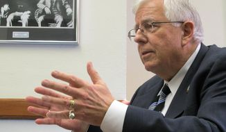 ** FILE ** Sen. Mike Enzi, R-Wyo., addresses reporters Wednesday, Feb. 19, 2014, at the Wyoming Capitol. (AP Photo/Ben Neary)