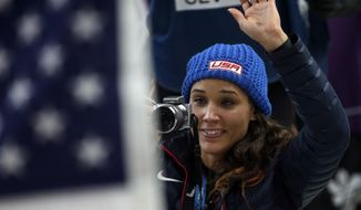 American bobsledder Lolo Jones takes pictures of her teammates after they won silver and bronze during the women's bobsled competition at the 2014 Winter Olympics, Wednesday, Feb. 19, 2014, in Krasnaya Polyana, Russia. (AP Photo/Michael Sohn)