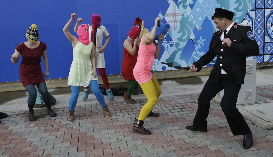 A Cossack militiaman attacks Nadezhda Tolokonnikova as she and fellow members of the punk group Pussy Riot, including Maria Alekhina, center, in the pink balaclava, stage a protest performance in Sochi, Russia, on Wednesday, Feb. 19, 2014. The group had gathered in a downtown Sochi restaurant, about 30km (21miles) from where the Winter Olympics are being held. They ran out of the restaurant wearing brightly colored clothes and ski masks and were set upon by about a dozen Cossacks, who are used by police authorities in Russia to patrol the streets. (AP Photo/Morry Gash)