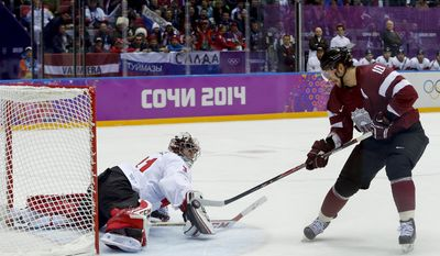 Latvia forward Lauris Darzins flips the puck past Canada goaltender Carey Price for a goal during the first period of a men's quarterfinal ice hockey game at the 2014 Winter Olympics, Wednesday, Feb. 19, 2014, in Sochi, Russia. (AP Photo/Julio Cortez)