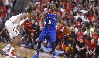 Texas Tech's Robert Turner defends Kansas' Naadir Tharpe (10) during their NCAA college basketball game in Lubbock, Texas, Tuesday, Feb, 18, 2014. (AP Photo/Lubbock Avalanche-Journal, Stephen Spillman)